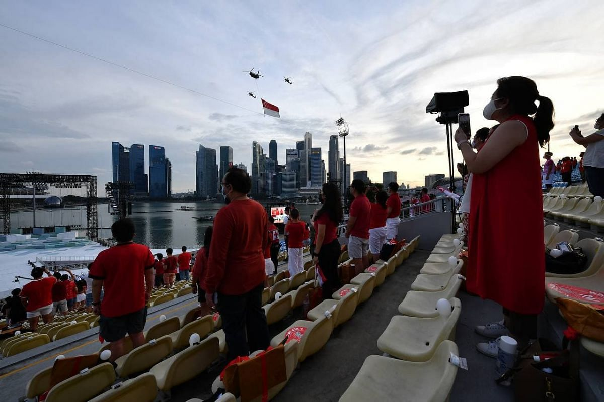 Spectators watch the state flag fly-past at the Marina Bay floating platform on Aug 21, 2021.