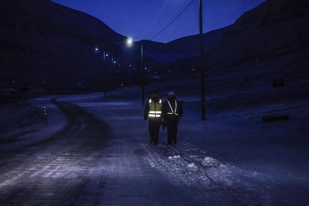 Two pedestrians wear reflective vests as they walk along a road in Longyearbyen in the afternoon on Feb 5, 2020.