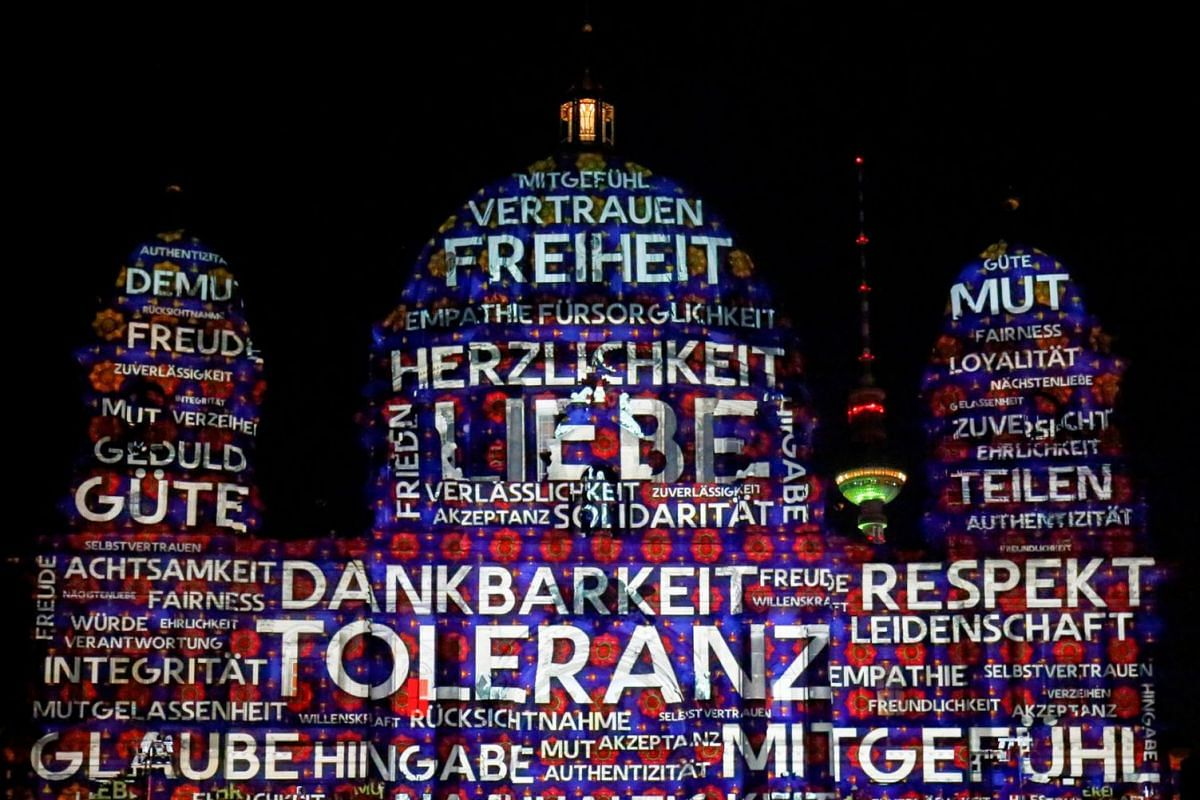 """The Berlin Cathedral (Berliner Dom) is illuminated during the Festival of Lights show in Berlin, Germany, September 3, 2021. Words read """"tolerance"""" and """"thankfulness""""."""