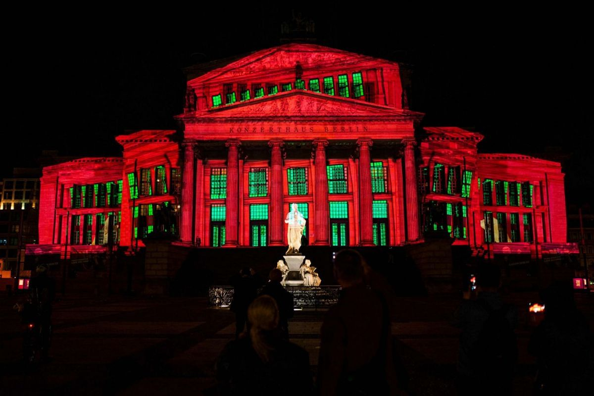 People gather in front of the Konzerthaus (Berlin Concert Hall) illuminated as part of the yearly Festival of Lights in Berlin on September 3, 2021.