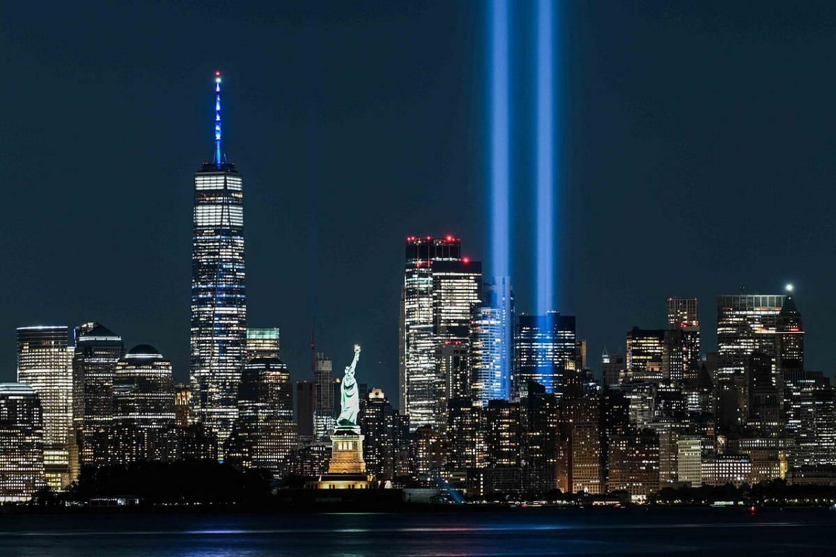 The Statue of Liberty shines near the Tribute in Light as part of the commemoration for 20th anniversary of the terrorist attack in New York City on Sept 11, 2021.