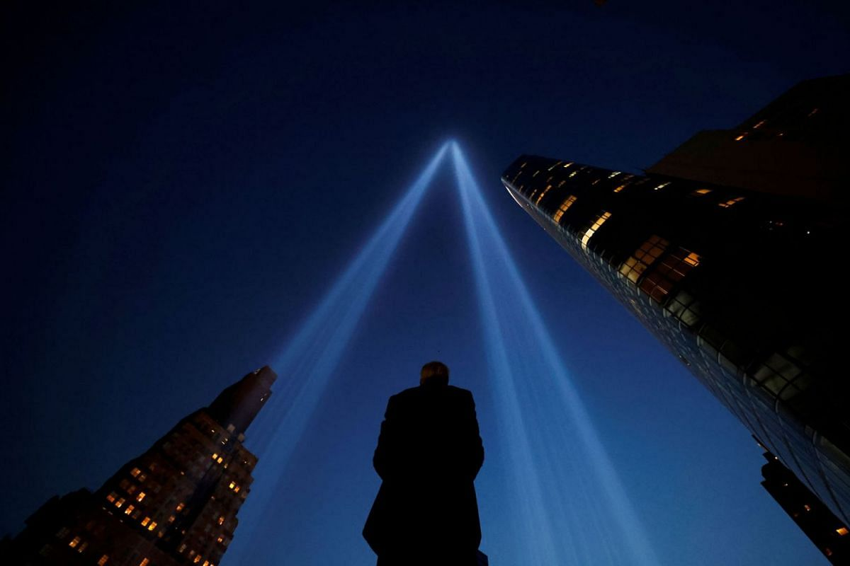 A person takes pictures of the Tribute in Light art installation on the day marking the 20th anniversary of the September 11, 2001 attacks in New York City, New York, U.S., September 11, 2021.