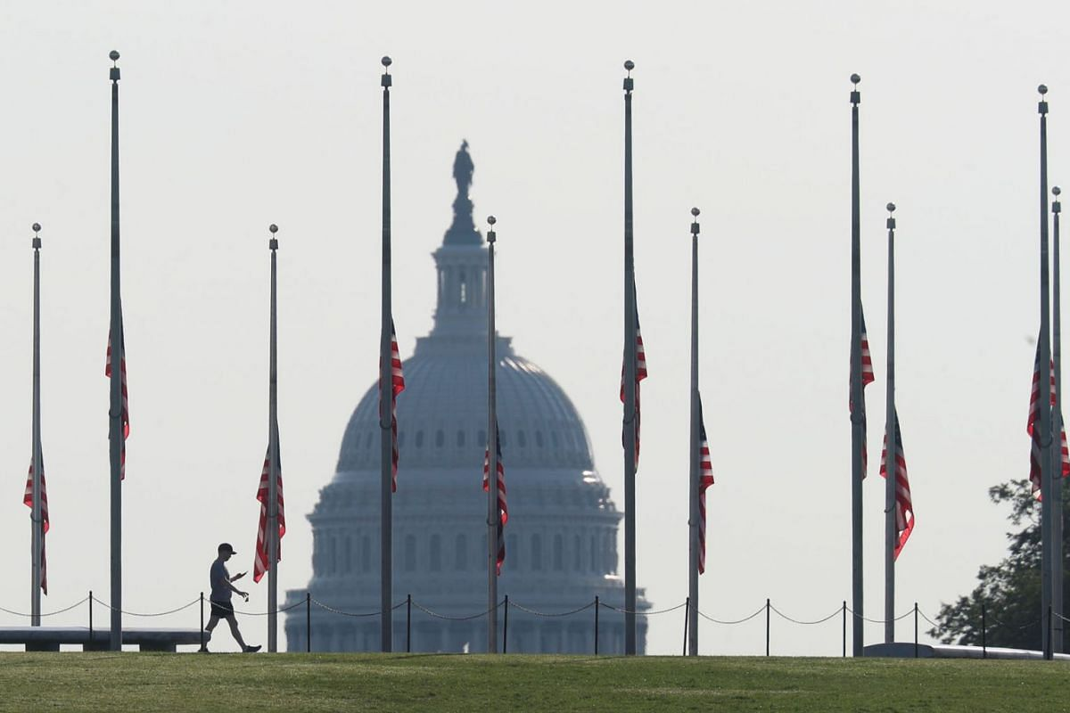 A visitor walks around the Washington monument as American flags are held at half staff in remembrance of the 20th anniversary of the September 11 attacks, on the National Mall near the U.S. Capitol in Washington, U.S., September 11, 2021.