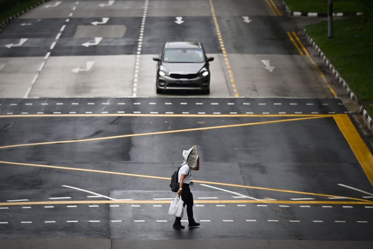 A man uses a newspaper to shield himself from a drizzle while crossing a road in Tampines on Sept 13, 2021.
