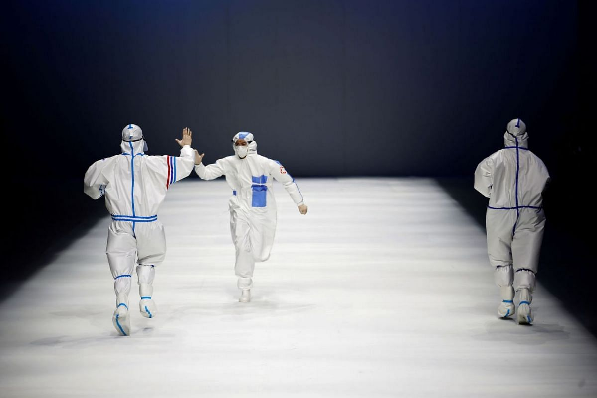 Models interact while they present protective suits made for medical professionals, designed by the Beijing Institute of Fashion Technology in collaboration with Dishang, during China Fashion Week in Beijing, China September 11, 2021.