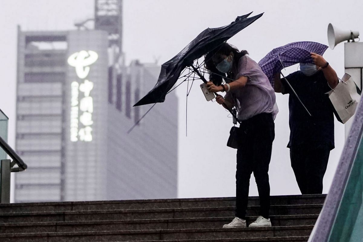 People hold umbrellas amid rainfall, as Typhoon Chanthu approaches, in Shanghai, China, September 13, 2021.