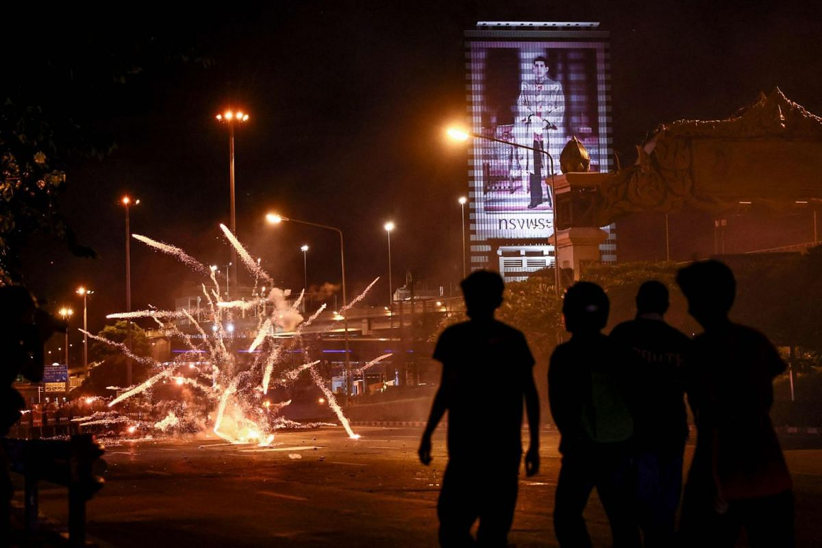 Fireworks launched by protesters explode in front of riot police during a demonstration calling for the resignation of Thailand's Prime Minister Prayut Chan-O-Cha over the government's handling of the Covid-19 coronavirus crisis in Bangkok on Septemb