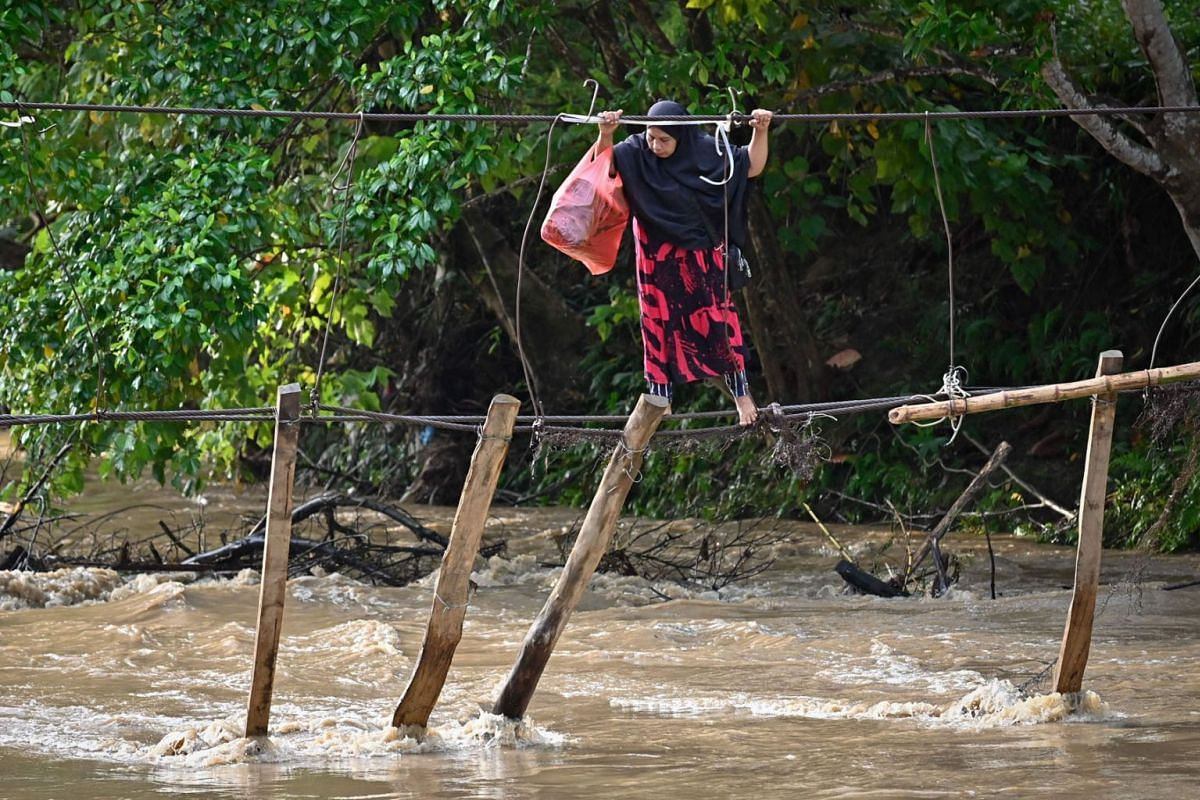 A woman crosses a river using the remains of a bridge, swept away during flooding the previous year, at Malela village in Luwu Regency, South Sulawesi, on September 13, 2021.
