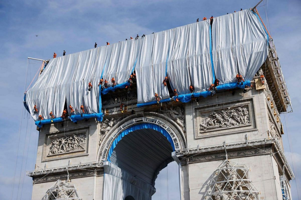 Workers unravel silver blue fabric, part of the process of wrapping L'Arc de Triomphe in Paris on September 12, 2021, designed by the late artist Christo.