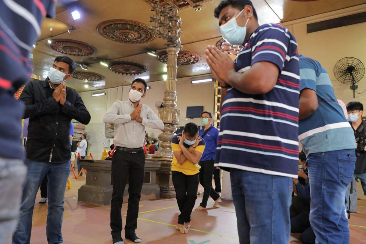 Migrant workers offering prayers at Sri Veeramakaliamman temple on September 15, 2021. They were the first batch of workers from Westlite Mandai dormitory to visit Little India under a  long-delayed pilot scheme that saw dormitory operators select el