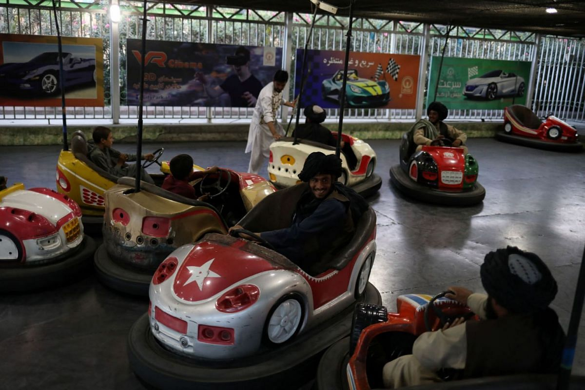 Taliban soldiers ride bumper cars in an amusement park in Kabul, Afghanistan, September 13, 2021.
