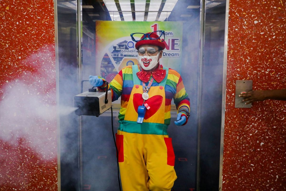 A photo released on September 14, 2021, shows Shaharul Hisam bin Baharuddin, 43, dressed as a clown, disinfecting a lift inside a shopping mall in Taiping, Malaysia, on September 10, 2021.