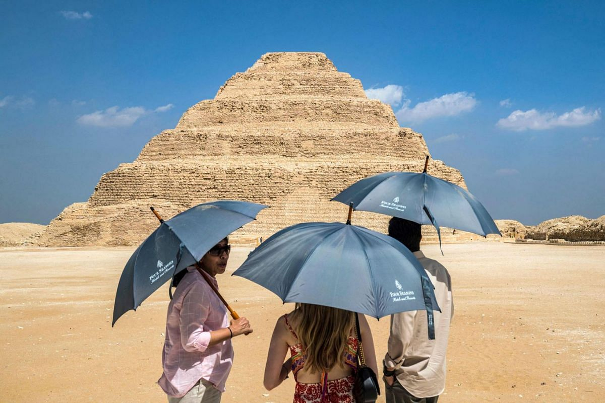 Visitors stand with umbrellas near the step pyramid of the third dynasty Ancient Egyptian Pharaoh Djoser (27th century BC) at the Saqqara Necropolis south of Egypt's capital Cairo on September 14, 2021.
