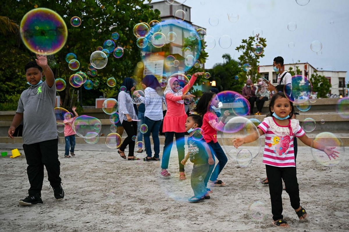 Local residents play with bubbles at Pantai Cenang in Langkawi on September 15, 2021, a day before the Malaysian holiday island is set to reopen to domestic tourists following closures due to restrictions to halt the spread of the Covid-19 coronaviru