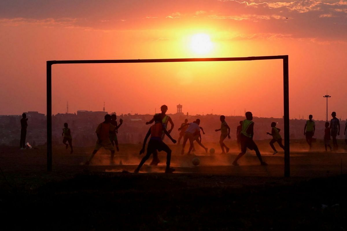 Locals play soccer on a dusty pitch in Soweto, South Africa, September 15, 2021.