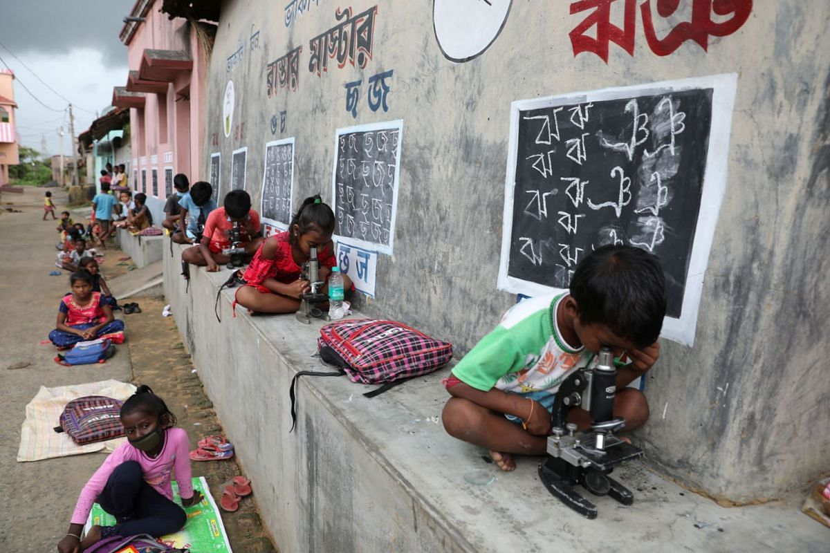 A photo released on September 16, 2021, shows children, who do not have access to internet facilities and gadgets, using microscopes as they attend an open-air class outside houses with the walls converted into black boards following the closure of t