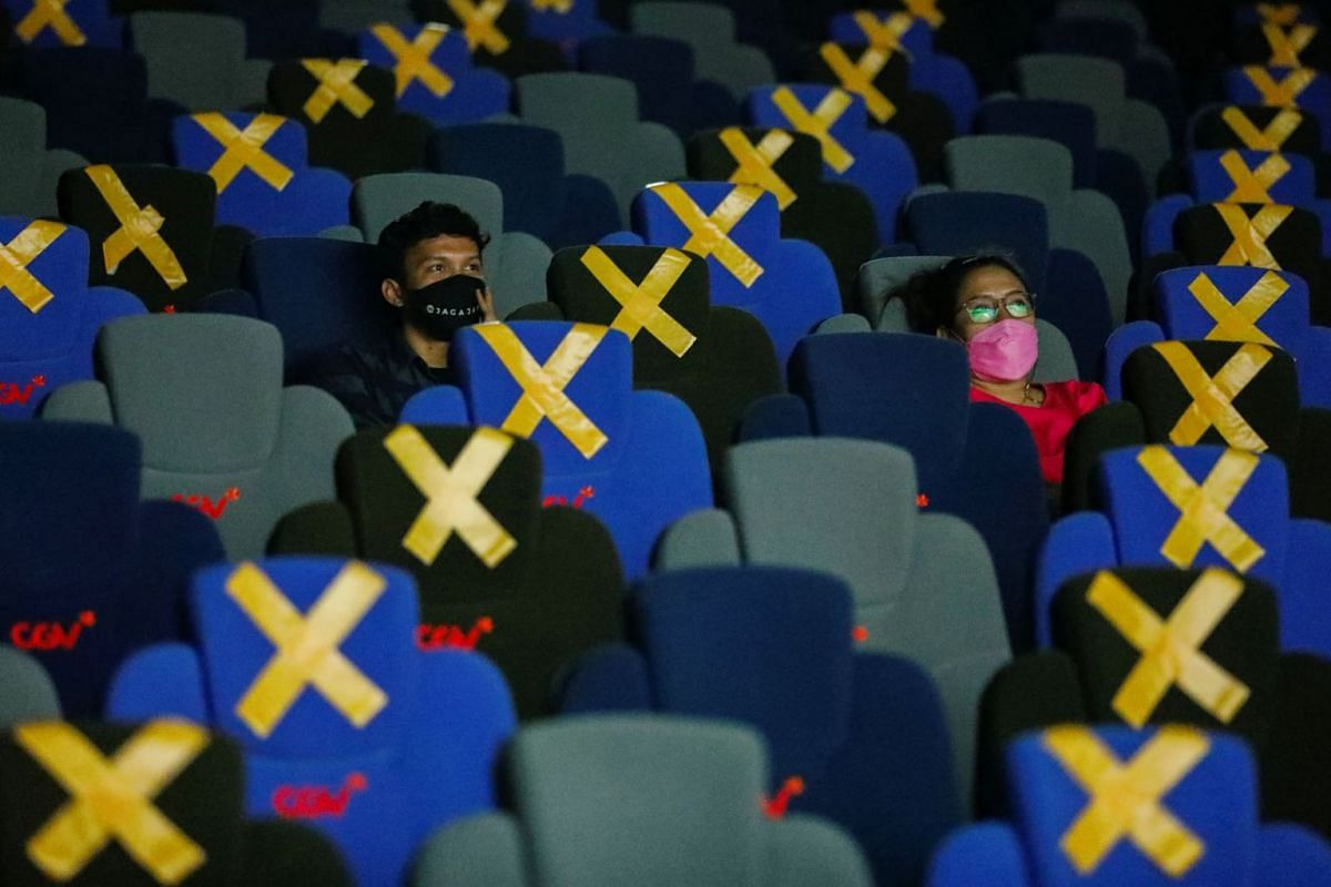 Visitors wearing protective masks watch a movie at a cinema as it is reopened after the ease of restrictions amid the coronavirus disease pandemic in Jakarta, Indonesia, September 16, 2021.