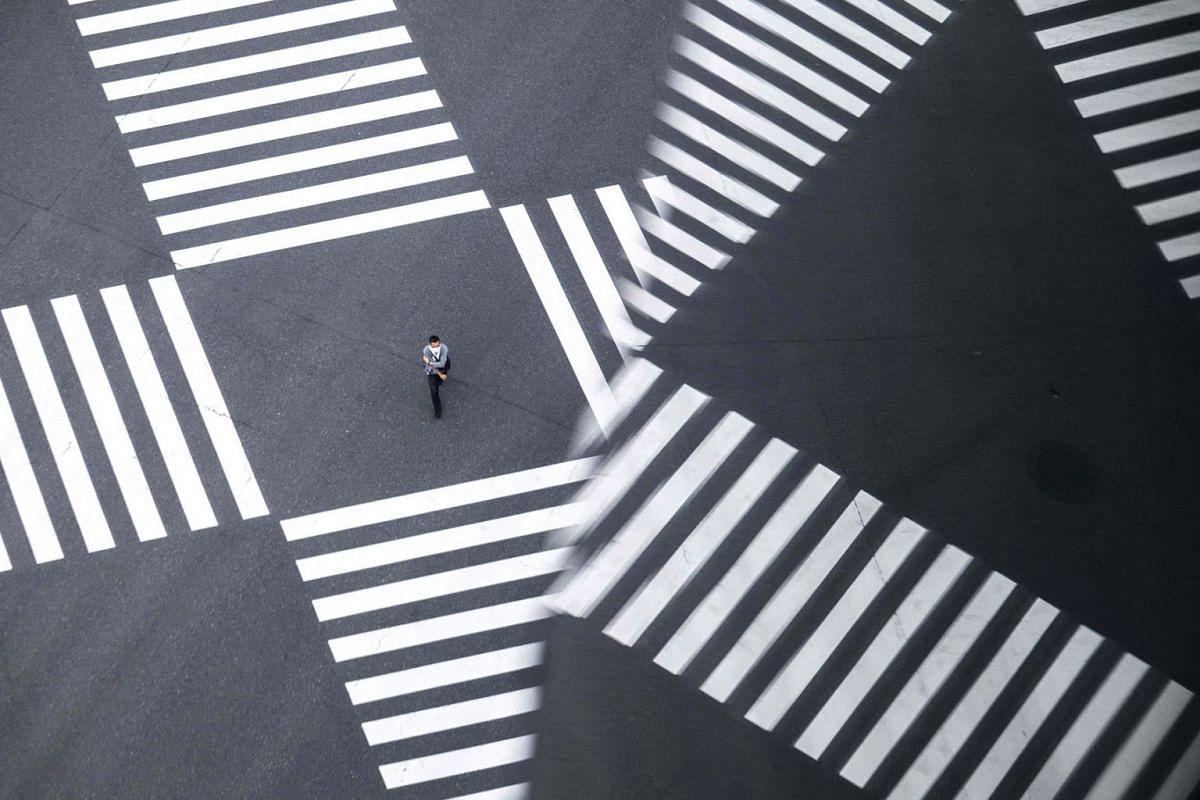 A man crosses a street in Tokyo on September 16, 2021.