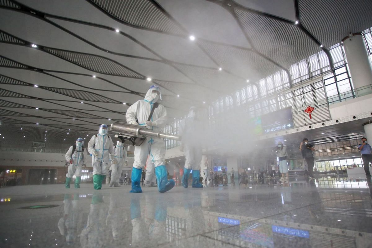 Firefighters spray disinfectant at the Yangzhou East train station in Yangzhou in China's eastern Jiangsu province on September 16, 2021.