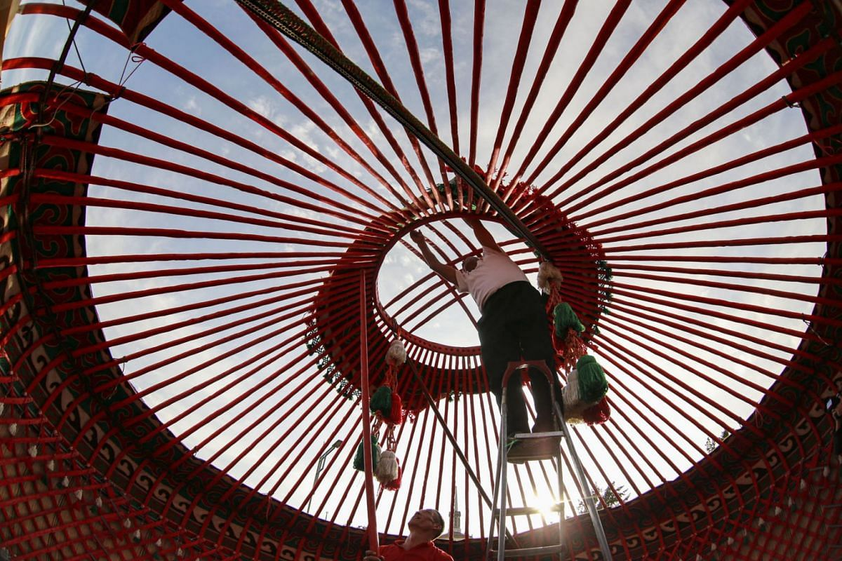 Kyrgyz men assemble a yurt for the upcoming World Festival of Epics of the World on the central square of Bishkek, Kyrgyzstan, September 22, 2021.