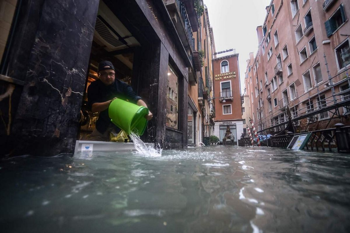 In this photo taken on Nov 15, 2019, a man drains water with a bucket from a shop in a flooded alleyway in Venice, two days after the city suffered its highest tide in 50 years.