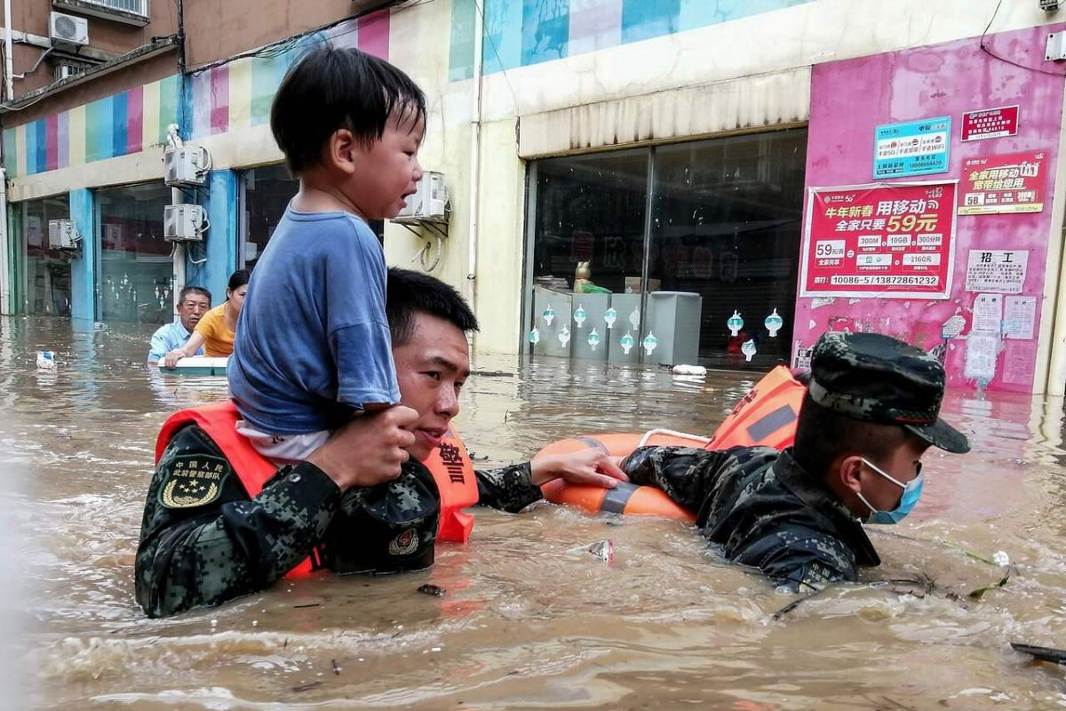 This photo taken on August 12, 2021, shows rescuers evacuating a child from a flooded area following heavy rain in Suizhou, in China's central Hubei province.