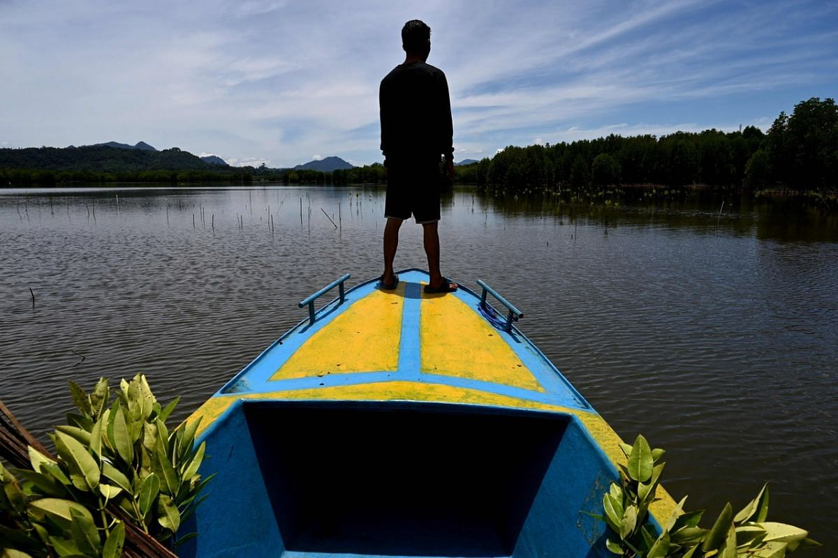 A student prepares to plant mangroves in Calang, in Indonesia's Aceh province, on Sept 15, 2021.