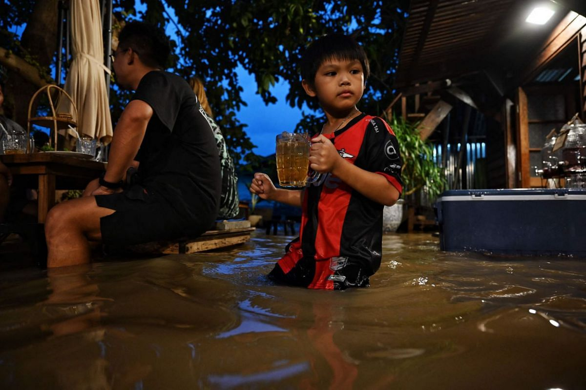 This photo taken on October 7, 2021, shows a young boy carrying a drink at the Chaopraya Antique Cafe, as flood water from the Chao Phraya River surges into the restaurant, in Nonthaburi province north of Bangkok.