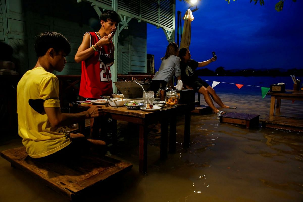 People eat food at a flooded restaurant, where patrons stand up from their tables every time the waves come in, on a river bank in Nonthaburi near Bangkok, Thailand, October 7, 2021.