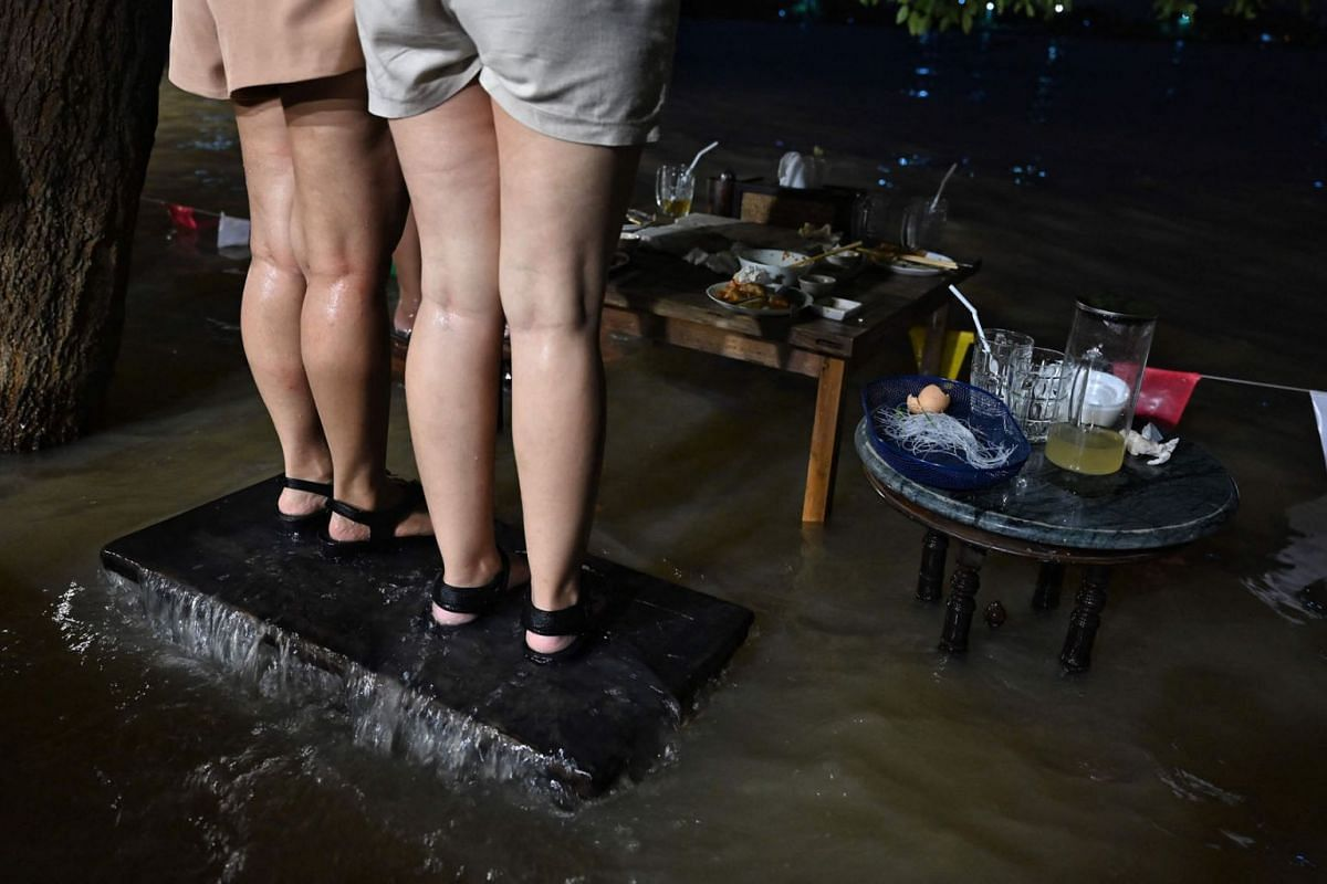 This photo taken on October 7, 2021, shows people standing on their chairs whilst enjoying dinner at the Chaopraya Antique Cafe, as flood water from the Chao Phraya River surges into the restaurant, in Nonthaburi province north of Bangkok.