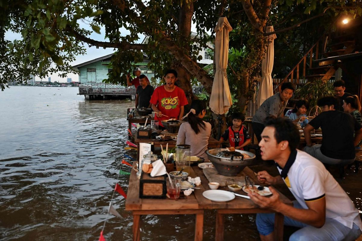 This photo taken on October 7, 2021, shows people standing up whilst enjoying dinner at the Chaopraya Antique Cafe, as flood water from the Chao Phraya River surges into the restaurant, in Nonthaburi province north of Bangkok.