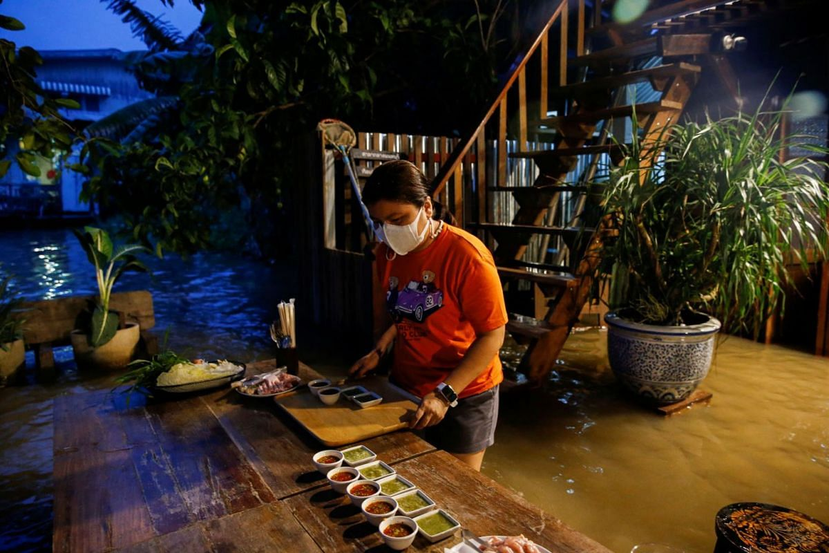 A staff member prepares food for customers at a flooded restaurant, where patrons stand up from their tables every time the waves comes in, on a river bank in Nonthaburi near Bangkok, Thailand, October 7, 2021.