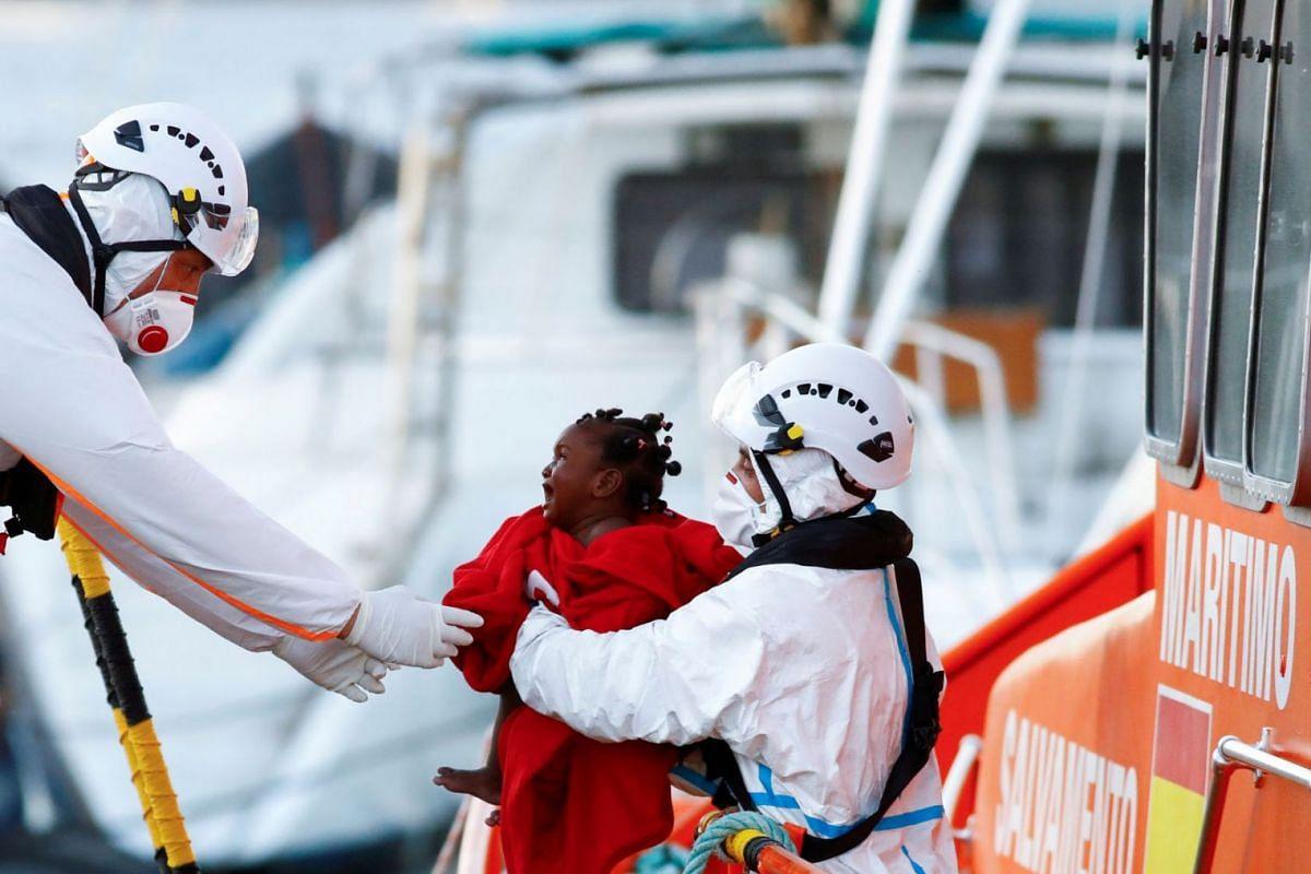 Lực lượng cứu hộ giúp một đứa trẻ di cư xuống tàu tuần duyên Tây Ban Nha, tại cảng Arguineguin, thuộc đảo Gran Canaria, Tây Ban Nha, ngày 10 tháng 10 năm 2021.