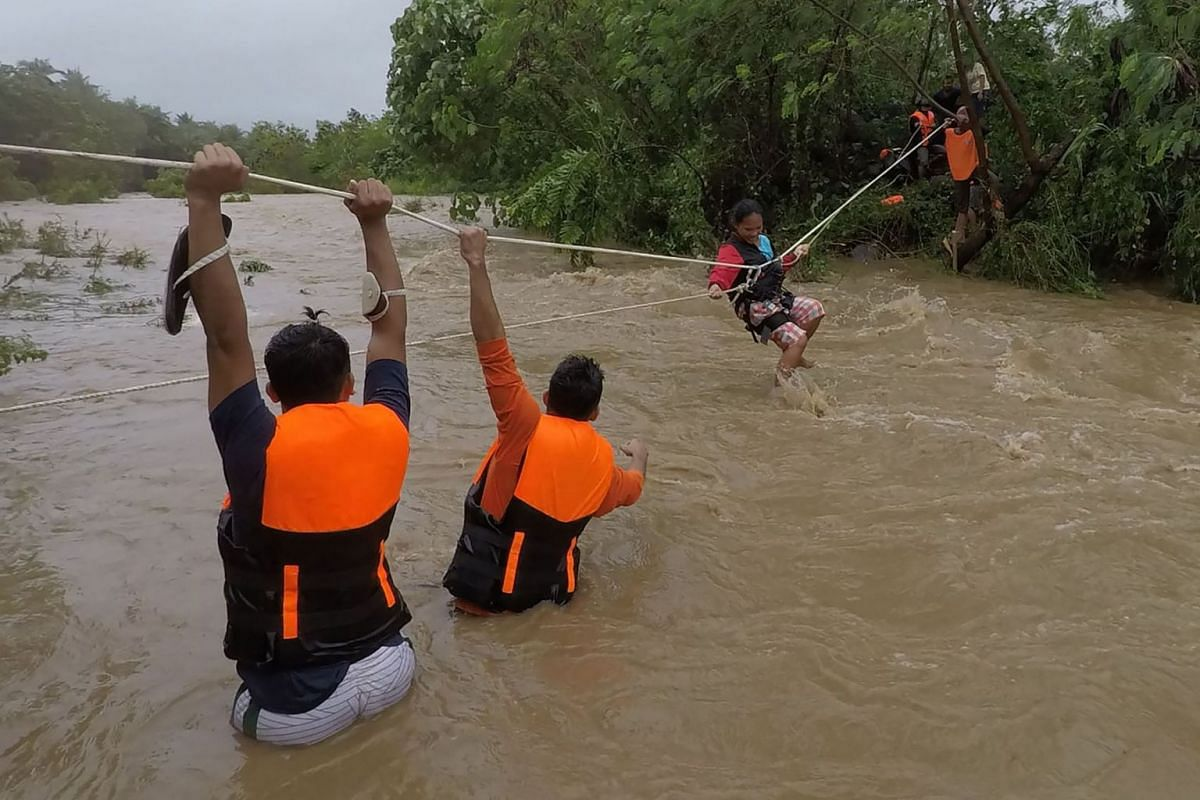 This handout photo taken on October 11, 2021 and received on October 12 from Gonzaga Municipal Disaster Risk Reduction and Management Office (GONZAGA-MDRRMO), shows rescuers evacuating residents from their homes near a swollen river due to heavy rain