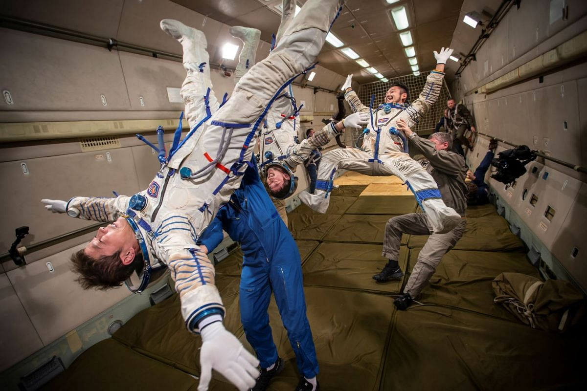A photo released on October 13, 2021, shows space flight participants Yusaku Maezawa and Yozo Hirano and back-up participant Shun Ogiso perform a zero-gravity flight while training ahead of the expedition to the International Space Station in the Mos