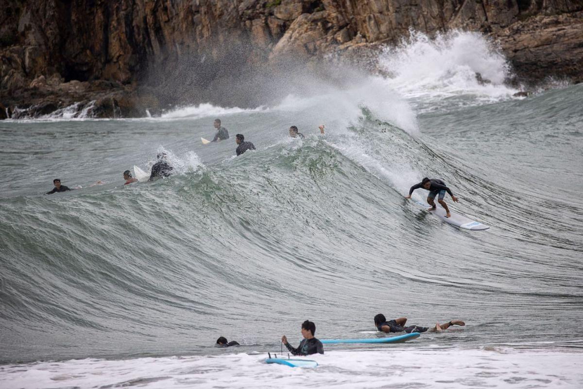 Surfers ride waves brought by tropical cyclone Kompasu in Big Wave Bay, Hong Kong, China, October 12, 2021.