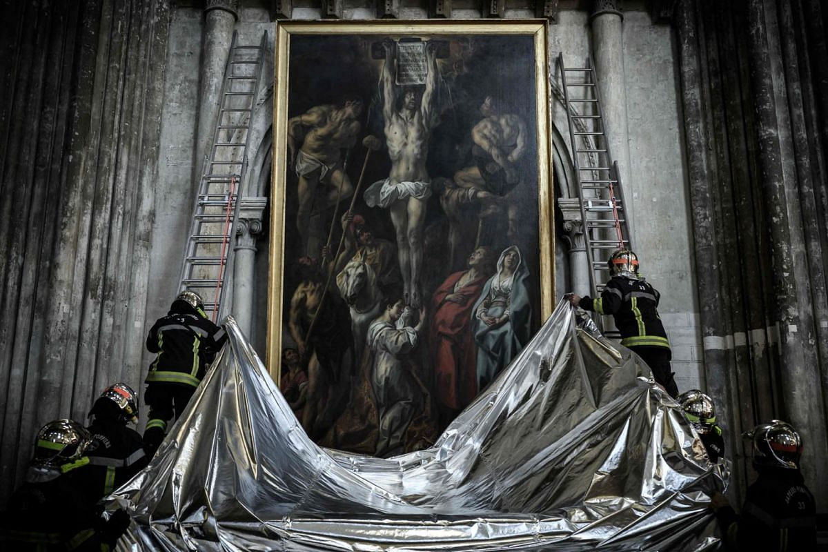 French firefighters protect a painting with a fireproof blanket during a fire drill aimed at preserving artworks displayed in the Saint-Andre cathedral in Bordeaux, southwestern France, on October 12, 2021.