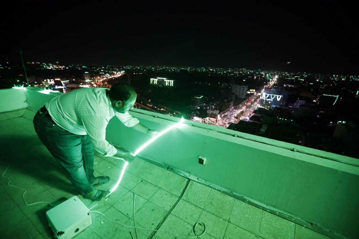 A Yemeni prepares green colorful lights at the roof of a building overlooking the city in preparation for celebrations of the Mawlid, marking the birthday of the Prophet Muhammad, in Sana'a, Yemen, October 12, 2021.
