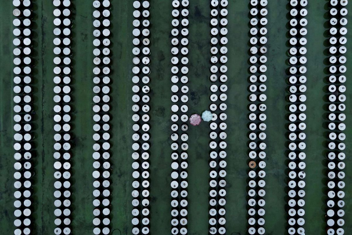This aerial picture taken on October 13, 2021 shows two visitors walking among soy sauce containers at a pickle factory in Yunlin county, an agricultural zone in the central west of Taiwan.