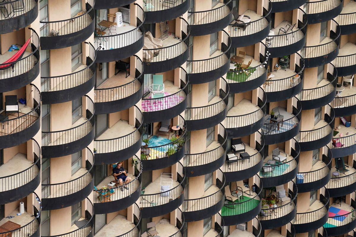 A man sits on his balcony amid a sea of balconies at an apartment building in Arlington, Virginia October 13, 2021.