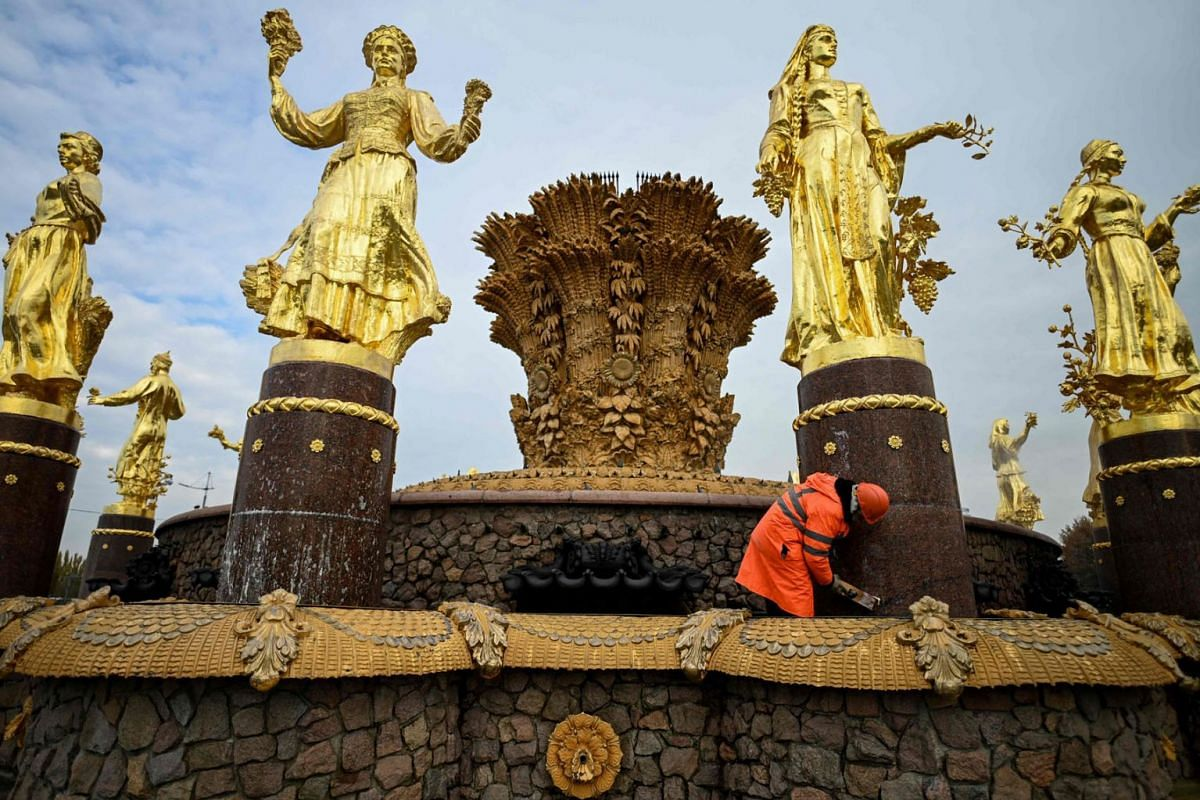 A municipal worker cleans the Druzhba Narodov (Friendship of Nations) fountain at the All-Russia Exhibition Centre (VDNKh) as part of the city's preparations for winter in Moscow on October 13, 2021.