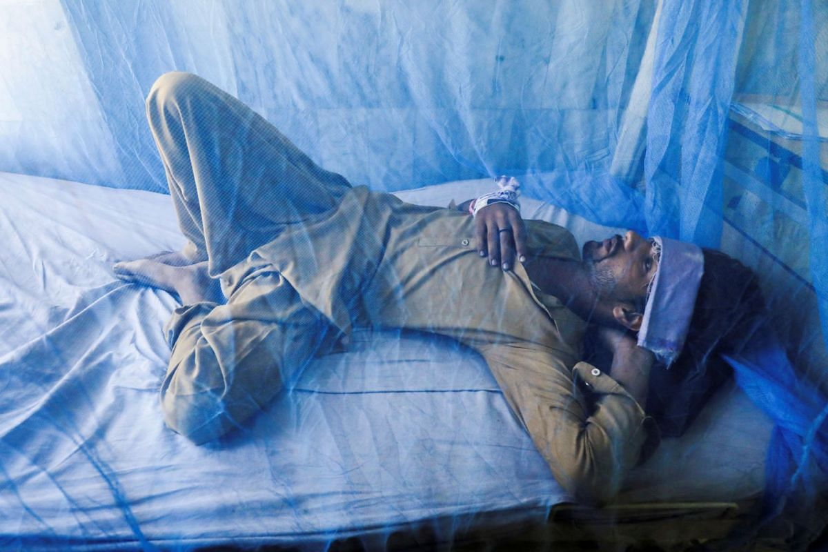 A patient, suffering from dengue fever, lies under a mosquito net inside a dengue ward at Lady Reading Hospital in Peshawar, Pakistan, October 12, 2021.