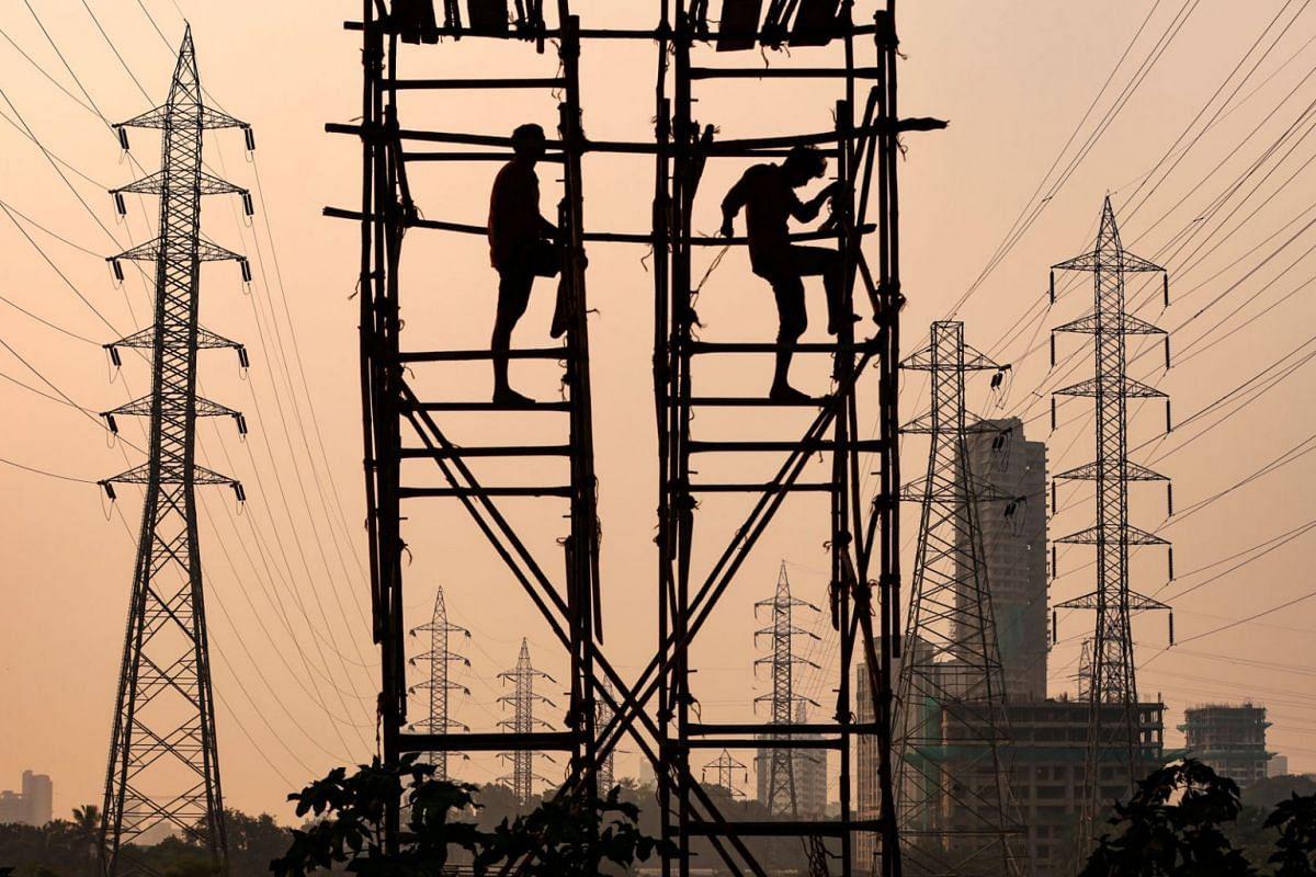 Labourers work next to electricity pylons in Mumbai, India, October 13, 2021.