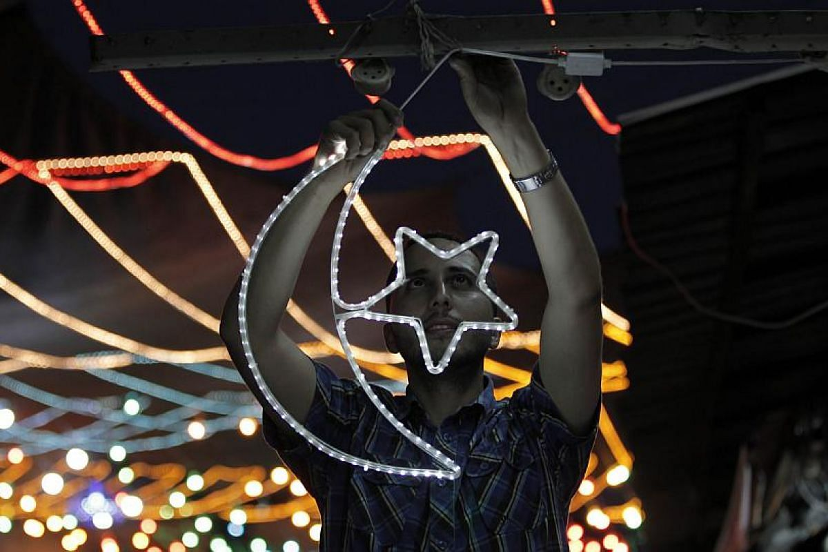 A Palestinian man decorating his shop with fairy lights near the entrance of the Al-Aqsa mosque compound, in the old city of Jerusalem.