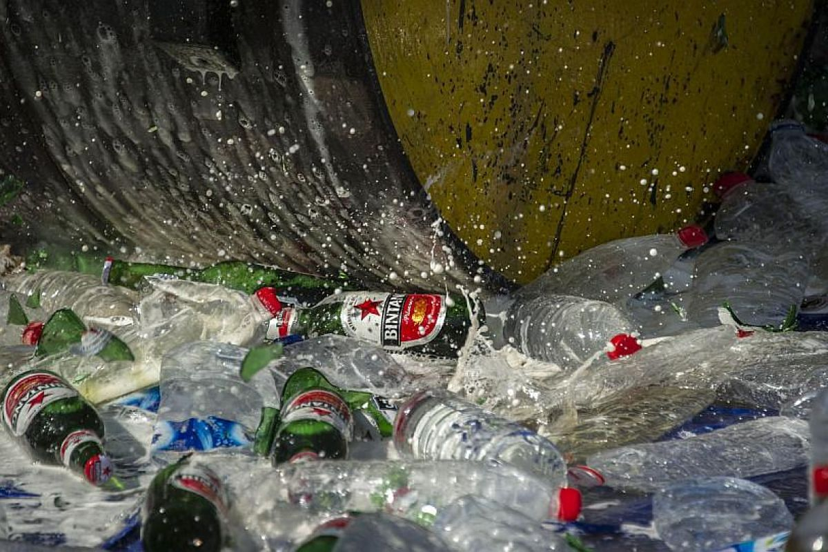 A steamroller running over bottles of alcohol at a police station in Jombong, East Java, ahead of Ramadan.