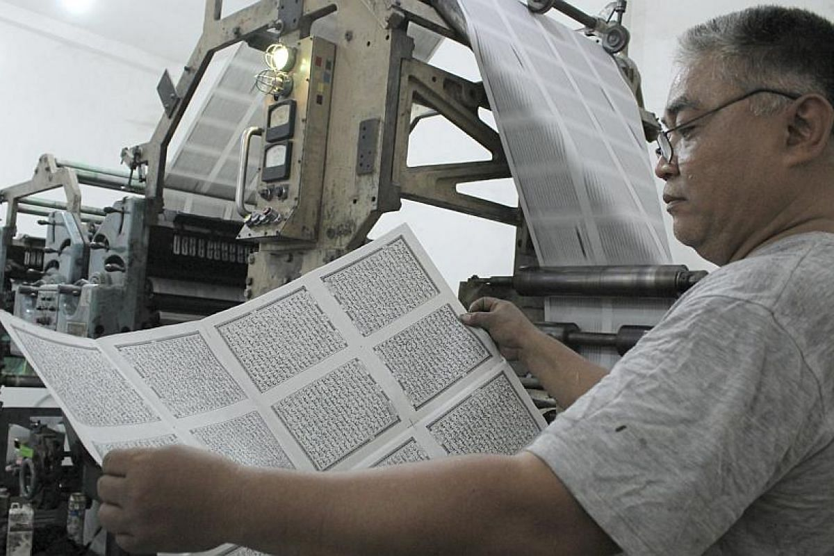 A worker checking a printout of the Quran in Surabaya, Indonesia. Orders for it  typically increase by 30 per cent before Ramadan.