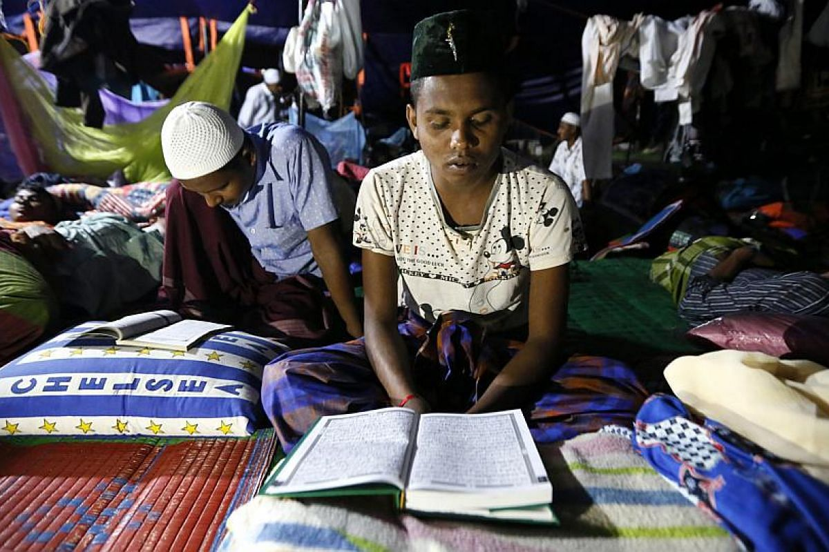 Rohingya Muslim migrants reading verses from the Quran on the first day of Ramadan at an Indonesian refugee camp in Bireun Bayeun, East Aceh.