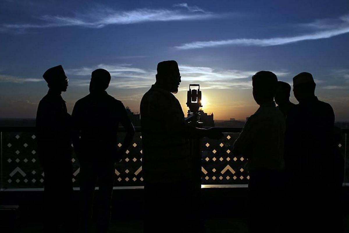 A Malaysian Islamic religious officer looking into a telescope for a sighting of the new moon to mark the start of Ramadan in Putrajaya, Malaysia.
