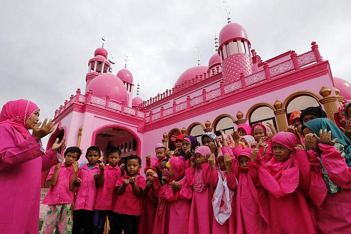 An Arabic teacher instructing Filipino Muslim children on the proper way of praying on the first day of Ramadan, outside the Pink mosque in Datu Saudi Ampatuan town, Maguindanao province.