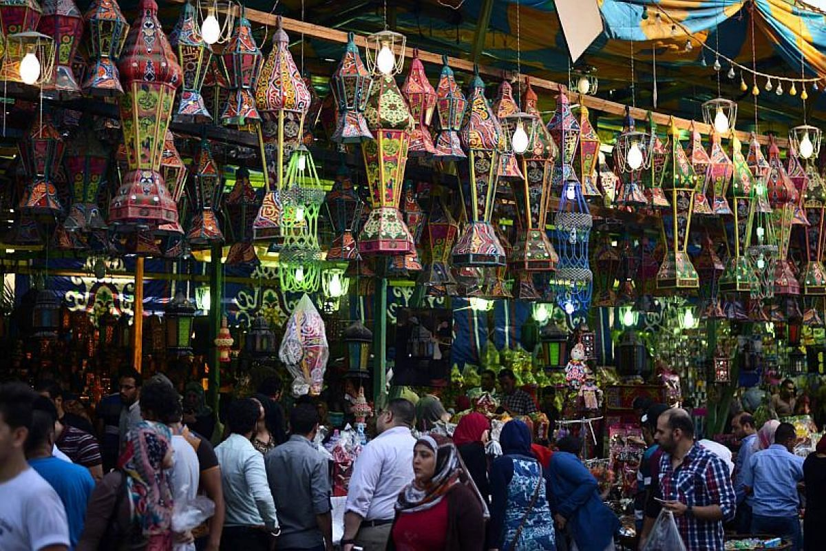 """Egyptians walking past traditional lanterns known in Arabic as """"fanous"""", which are traditionally sold during Ramadan, in the Saida Zeinab district of Cairo."""